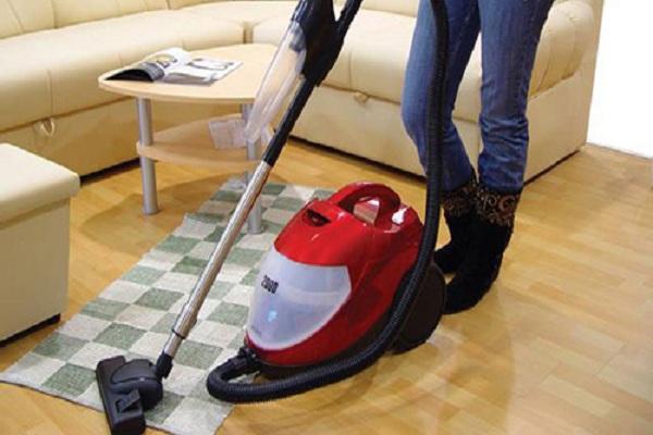 Sử dụng máy hút bụi làm sạch tấm thảm chùi chân hàng ngày.