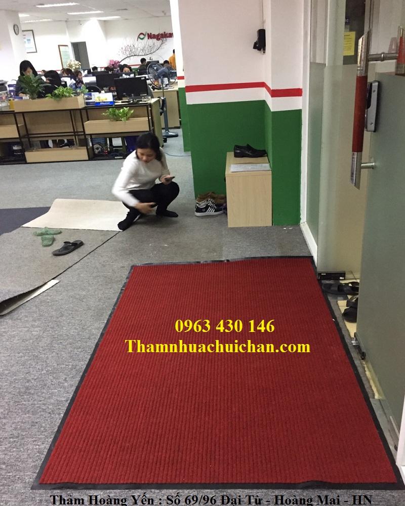 Thảm chùi chân sợi len đế cao su màu đỏ trầu trải sảnh văn phòng.
